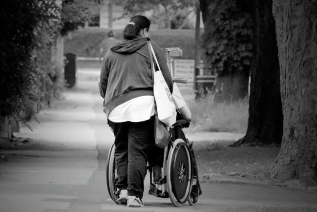 женщина катит инвалидную коляску