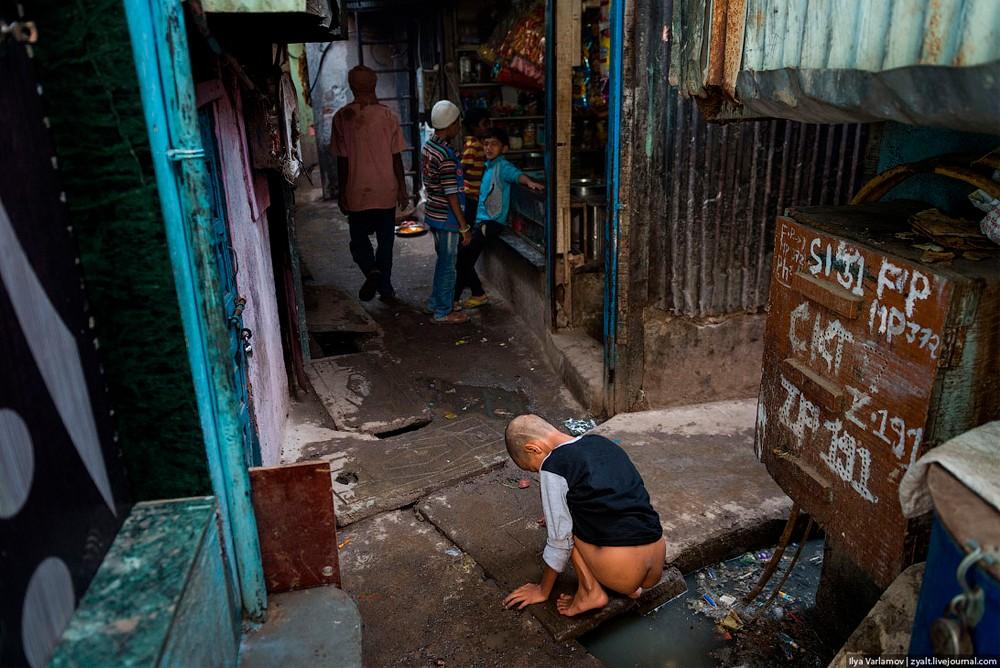 Какающий мальчик в трущебах Мумбаи