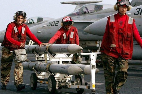 Военные транспортируют ракеты AIM-120 AMRAAM на палубе авианосца USS Kitty Hawk 10 марта 2003 года