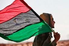 Мужчина несёт флаг Ливии