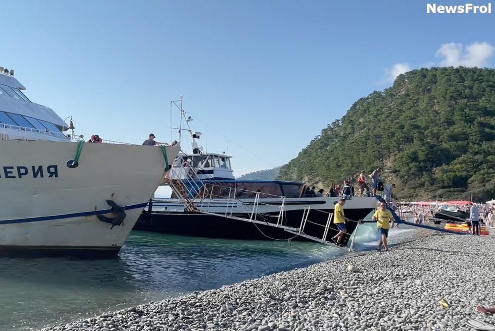 Геленджикские прогулочные корабли врезаются в галечный берег, чтобы высадить туристов на берег