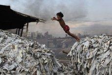 Ребенок прыгает через мусор в Хазарибахе, Дакка, Бангладеш, 9 октября 2012 года.