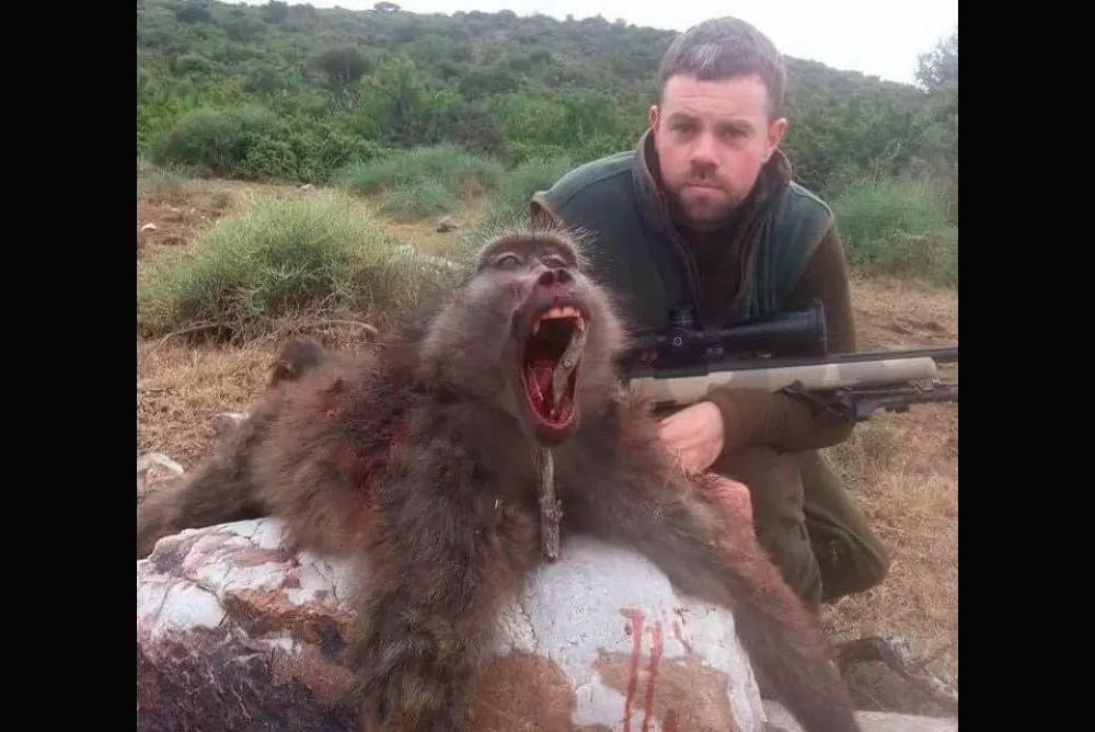 Турист Мики Джордан позирует с трупом бабуина после того, как застрелил его