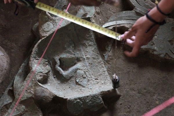 Археологи измеряют маску, найденную в гробнице жрецы мочика в 2013 году