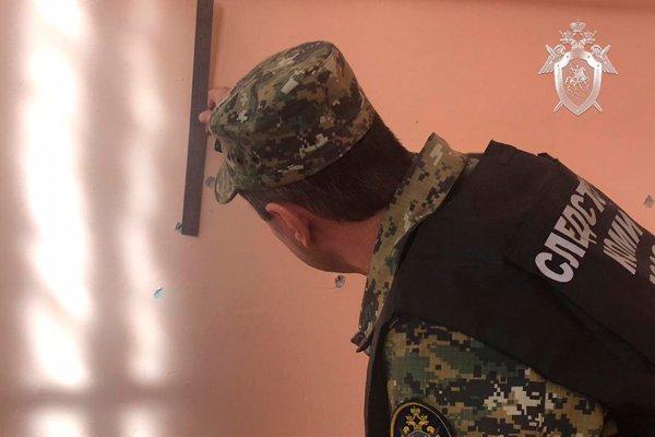 Следователь изучает повреждение стен от выстрелов картечью в керченском колледже