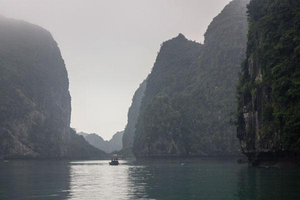 Виды бухты Халонг. Карстовые скалы. Пейзаж с лодкой.