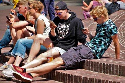 Молодые люди с мобильными телефонами