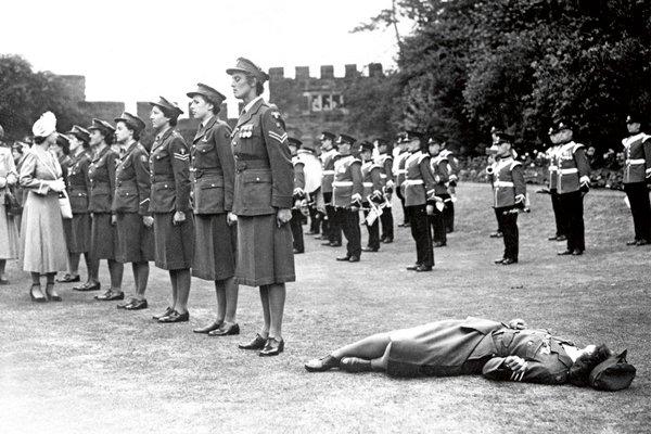 Во время осмотра принцессой Елизаветой почётного караула, одна из девушек потеряла сознание из-за жары, Англия, 6 июля 1949 года