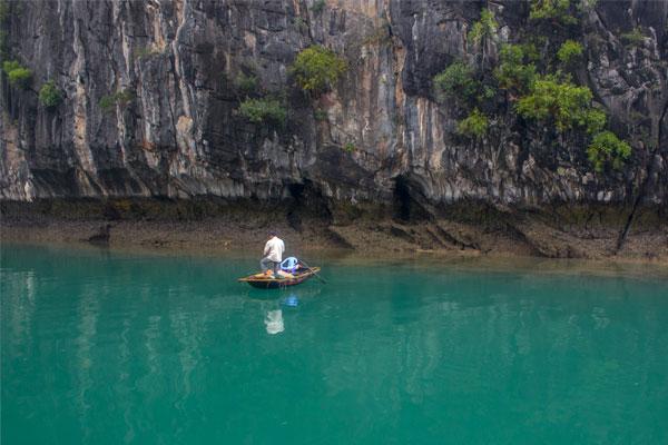 Виды бухты Халонг. Рыбак на лодке.