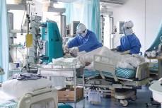 Врачи помогают пациенту с коронавирусом