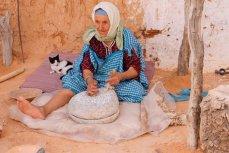 Пожилая тунисская женщина готовит еду