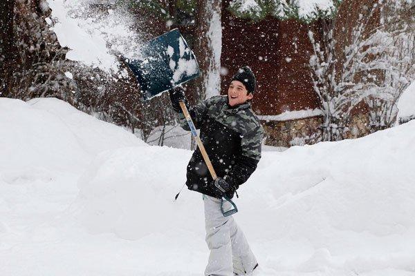 Мальчик убирает снег
