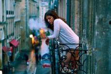 Девушка курит на балконе