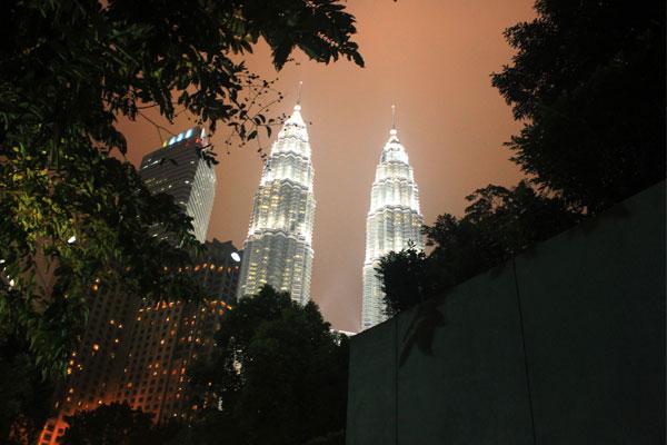 Башни Петронас среди зелени Центрального парка в Куала-Лумпуре. Малайзия.